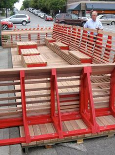 'parklet' programme which turns transportation infrastructure into public spaces. The design features a deck-like structure  in place of two  parking spots and includes built-in seats and wood-cubed tables.