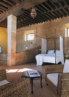 Esta antigua edificación agrícola de alto techos permite colocar una gran cama de dosel de hierro con una zona de estar.