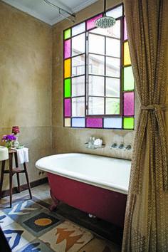Baño rústico con ventanal de vidrio repartido, piso de calcáreos, antigua bañera y cortina alternativa en una casa reciclada del Bajo San Isidro.