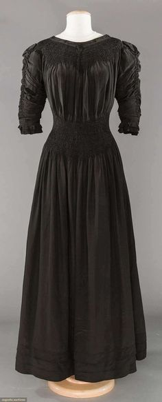 """BLACK SILK LIBERTY & CO. AESTHETIC DRESS, 1890-1905  -  Lot: 239 May 9, 2017 - CATALOG SALE -  Sturbridge, Massachusetts Unlabeled, black China silk, smocked yoke & deep midriff band, embroidered bands at neckline & on sleeve edge, 3 tucks to skirt hem, 14 pair self covered buttons to back, B to 36"""", W 24""""-30"""", L 58"""", (small hole on right sleeve, stains on skirt back) very good."""