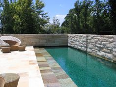 traditional styled family pool with automated cover behind stone wall. pool finished with bisazza glass tiles and sandstone paving designed by Grodski Architects