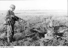 Red Army soldier emerges from his foxhole under the watchful eye of a German grenadier with an MP40 SMG, 1941-42. The flat terrain in many parts of European Russia made long defensive lines, comprising both trenches and individual positions, a routine occurrence.