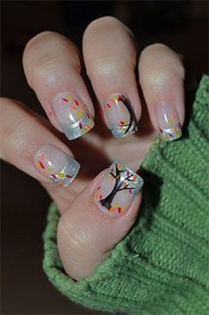 Candy colored leaf nail art design. A cute leaf nail art design that features light blue French tip with trees and multi colored leaves falling from it.