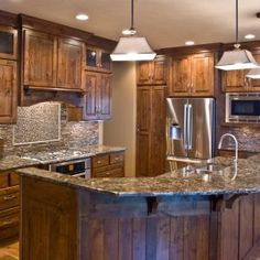 corbels, cabinets, cabinetry, kitchen, wood, wooden, custom, crown molding, custom hood, panelized ends, furniture base, arched bottom, island, sink in island, appliance panels, knotty alder, cambria