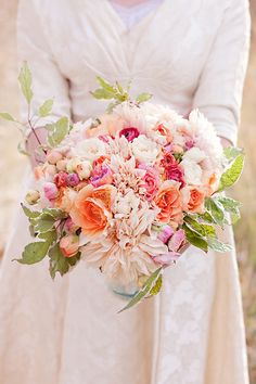 Pretty peach, tangerine, and coral bridal bouquet featuring dahlias, roses, and ranunculus.