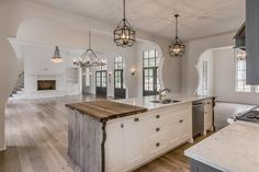 Mediterranean kitchen features a pair of Suzanne Kasler Morris Lanterns illuminating a white kitchen island fitted with reclaimed wood end pieces topped with grey and white marble fitted with a stainless steel dual sink next to a butcher block chopping board.