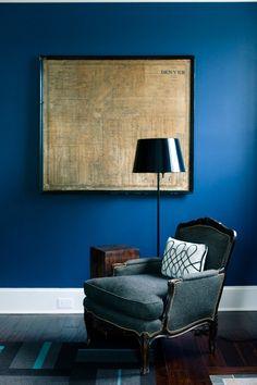 Blue painted wall, art, chair, pillow