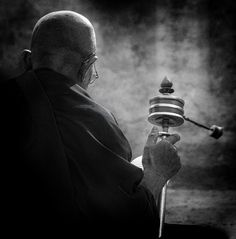 Buddhist monk sitting at the Buddha stupa in Kathmandu, Nepal for prayers while turning his prayer wheel.