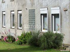 Verwitterte graue Fassade eines Wohnhaus mit vielen Fenstern in Oerlinghausen bei Bielefeld im Teutoburger Wald