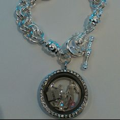 """CUSTOM Glass memory locket 925 plated bracelet I love these! I can customize these to fit lots of themes! There are many options, so please let me know if you have ideas for a bracelet. This particular piece features a 1"""" glass locket with rhinestones. The charm bracelet is 925 silver plated with a beautiful design and closure. Measures about 8.5"""" lying flat. The charms included are a pink heart, a bible and a rhinestone cross. The face plate is a man and woman with a child. handmade Jewelry…"""