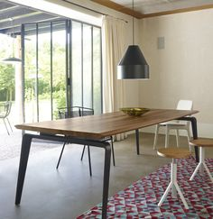 Odessa Dining Table. This solid wood table is truly elegant with its floating top and solid steel legs. The top is possible in European oak or walnut with black or white-lacquered feet.  Dims from 180 to 260 cm. Shown here with new Hex Hex rug in almond tones.