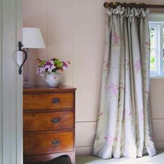 Susie Watson Designs - Susie Watson Designs Fabric Collection - A wood chest of drawers with a clear and white table lamp, a jug vase, and floor-length grey, pink and green floral curtains