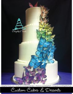 Sweet 16th four Tier Cake with Edible Cascading Rainbow Butterflies, Delightful Treats |  #MonarchButterflyCake #ButterflyCake #Sweet16thButterflyCake #ButterflyWeddingCake #CakeWithButterflies #EdibleButterflies #ButterflyCakeDecoration #BeautifulButterflyCake #CascadingRainbowButterflyCake #RainbowCake #RainbowButterflyCake