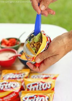 The whole concept is that these are tacos on the run…or walk. Take a snack sized bag of Fritos or Doritos andcrush them up. Open the bag and fill it with taco meat and all of your favorite taco toppings. Then you're  free to roam, work the crowd, or watch the game without being tied down to a table.