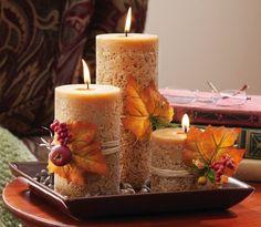 arrangement de bougies cylindriques décorées de feuilles et baies rouges en tant que centre de table automnal