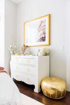 Stylish and contemporary bedroom featuring Bungalow 5 Jacqui 3-Drawer and gold ottoman