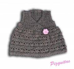 Vestido para niña realizado en ganchillo en color marrón. Se cierra con dos corchetes y lleva una flor en rosa como detalle.