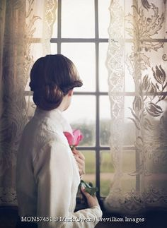Trevillion Images - vintage-woman-with-rose-by-window