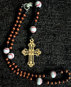 """This rosary was hand strung on a shamballa bracelet cord for strength using natural wood beads, an ornate wooden cross and baseballs for the pacers. It measures 18"""" around with a 6"""" string including the cross. Perfect to hang on the rear view mirror or on a lamp."""