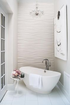Romantic bathroom features an accent wall clad in wavy tiles alongside a crystal chandelier hanging over a corner freestanding tub and floor mount tub filler as well as a marble Saarinen Side Table.