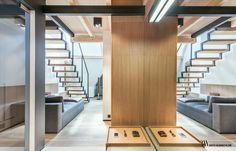 Wnętrze holu z tapicerowaną leżanką oraz z ażurowymi schodami na antresolę. www.bartekwlodarczyk.com