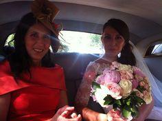 Magdalena con su madre, dentro del coche, con un tocado de ala con plumas y flor en color dorado y coral, una madrina muy elegante.