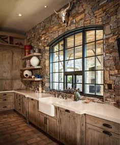 Beautiful Houston ranch house kitchen with French oak cabinets, stone wall, and metallic steer head. Designed by Thompson Custom Homes. | Stylish Western Home Decorating