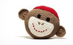 """Almofada de crochet macaco da peúga. De aprox. 13 """" de diâmetro, é feito com o coco marrom, creme branco e vermelho."""