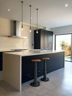 The island includes a breakfast bar with a tapering worktop in arctic ice Corian