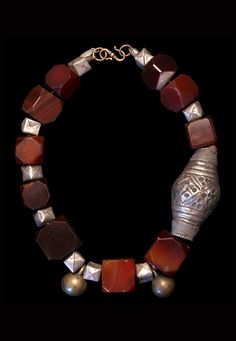 by Marion Hamilton | Carnelian cubes cut in the 19th c. in Idar Oberstein are interspersed with folded silver beads from Thailand. Two old brass bells from Nigeria and a large silver bead from Afghanistan complete the necklace. | $950