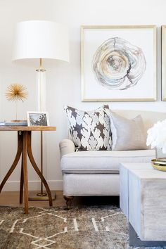 Beautiful living room features side by side agate art placed over a light grey linen roll arm sofa next to a round wood end table facing a weathered wood block coffee table atop a gray Greek key rug.