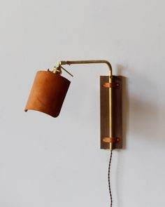 The custom made Ava Wall Sconce has a black walnut backplate , a brass arm and a hand sewn leather shade. The brass arm articulates to fulfill many different lighting needs . It can provide up lightin