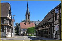 Photo du Musée ''Etappenstall'' ou Musée du Relais d'étape et des belles maisons alsaciennes à pans de bois dominées par l'église protestante du XIXe siècle, dans la rue du Général de Gaulle à Erstein. Photos d'Erstein, tourisme en Alsace.