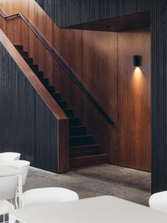 The dark walnut wood wall treatments contrast with the light white decor nicely.