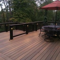 Tigerwood decking. Installed with hidden fastener system. Black composite posts and top rail with black aluminum ballisters.