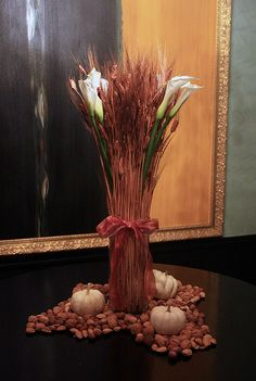 Give your family and friends a festive welcome by going grand in the entryway or on a fireplace mantle by showcasing a tall centerpiece of wheat stems interspersed with long-stemmed white flowers such as calla lilies or gladiolas. Since this is a table or surface that is primarily for display, surround the vase with nuts in their shells and white pumpkins.