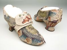 Shoes, 1760-1780, Cream silk brocaded in close floral pattern in coloured silks and metal thread. Bound with cream silk ribbon over linen. Round toes. Fastening by a pair of straps with buckles of metal set with stones. Brocaded heel.