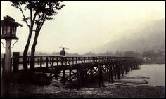 "MAN WITH AN UMBRELLA ON THE ""MOON CROSSING BRIDGE"",  WALKING IN SILENCE TOWARD KYOTO'S MISTY MOUNTAIN"