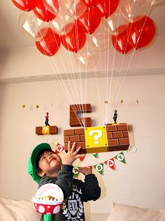 いっぱいのバルーンに吊られて宙に浮かぶハテナブロックと男の子の画像