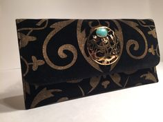 Handmade metal antique hardware medallion with precious stone... and premium velvet with calligraphy pattern with a signature flap front clutch.