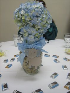 Centerpieces,vases filled with peanuts,blue hydranges and elephant attached