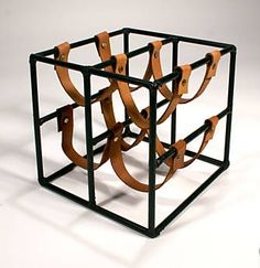 Uses metal bars and strap leather to hold wine bottles.
