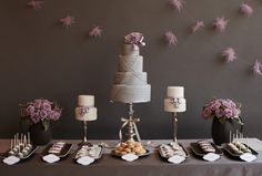 Grey and Lavednar sweets table. Sweets Stylist Amy Atlas designed this yummy-looking table with custom purple garland, tiered grey cakes by The Caketress, coordinating cupcakes by Erica OBrien Cake Design, and ivory and lavender cake pops from New York Cake Pops. Click here to get more sweets table ideas from Amy.