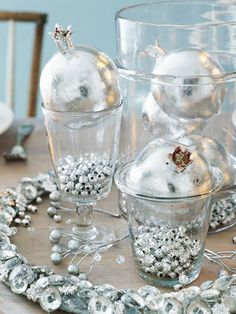 Silver Bells :: Give your table some bling this Christmas with silver-leaf fruit and plenty of shiny baubles. To make these silver pomegranates, paint artificial fruit with sizing adhesive, apply sheets of silver leaf, and burnish with a clear, dry brush. For a sparkling surround, hot-glue buttons and rhinestones to a slender wreath form and place on the table. Fill juice glasses with small silver beads and top with shiny pomegranates.