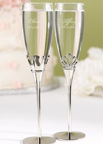 "Enjoy your first toast as bride and groom with these sparkling flutes fit for a king and queen! The groom's flute features a crown in likeness of a king and the bride's flute sparkles with rhinestones in likeness to a queen's tiara. You will definitely feel like royalty with this toasting flute set! Features and Facts: Flutes are 10 1/4"" tall. Flutes are personalized with two lines of personalization such as bride's name and wedding date on one flute and groom's name and wedding date on the…"