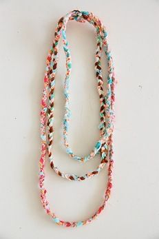 scrap fabric necklaces.  I have been trying to perfect this. Having trouble getting the strands to no bend and twist and to instead be flat.  Also experimenting with weaving in broken bracelets/ beads. Having fun!