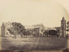 Photograph of the front of the Sassoon Hospital in Poona, now known as Pune. The building is in the neo-Gothic style with a tower to the far right. There are a few trees on the grass in the foreground and there is a man sitting under a tree to the right.