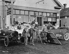 """movie crew and actors film a scene in an adaptation of Sinclair Lewis's """"Free Air"""" in front of a general store. 1921. Rosemount, MN"""