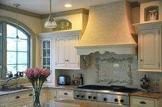 The range hood in this kitchen is covered in tiny mosaic tiles — a riff on convention, but it works because it approximates the rough look of a more traditional French country surface. The raised detailing on the backsplash enhances the sense of dimension.