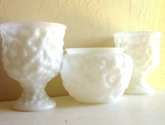 Three matching white milk glass vases - 2 pedestal dishes and 1 bowl all with a bumpy textured design. They are made by the E.O. Brody Company. I